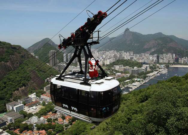 A man disguised as Santa Claus travels atop the Sugar Loaf cable car on December 21, 2012 in Rio de Janeiro, Brazil. Photo: MANOEL PAREDES, AFP/Getty Images / AFP