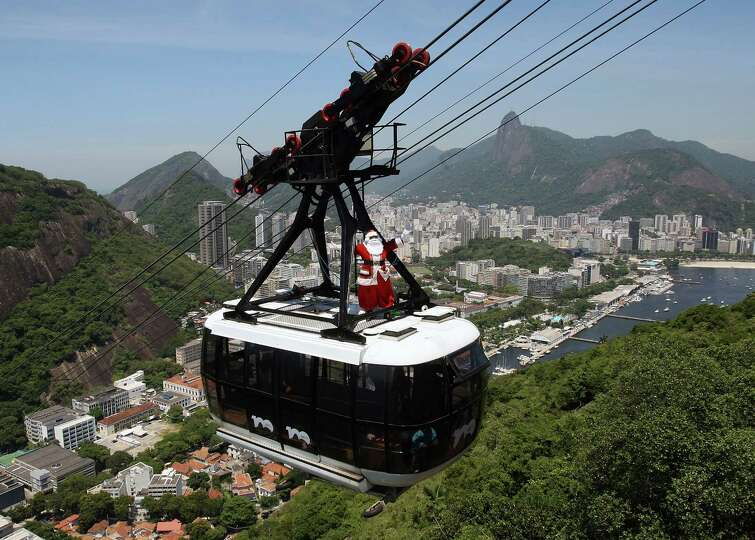 A man disguised as Santa Claus travels atop the Sugar Loaf cable car on December 21, 2012 in Rio de