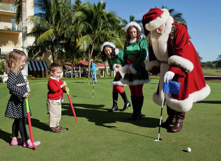 Carina Ballard, 6, left and her brother, Blake, 3, play golf with Santa Claus and his elves during t