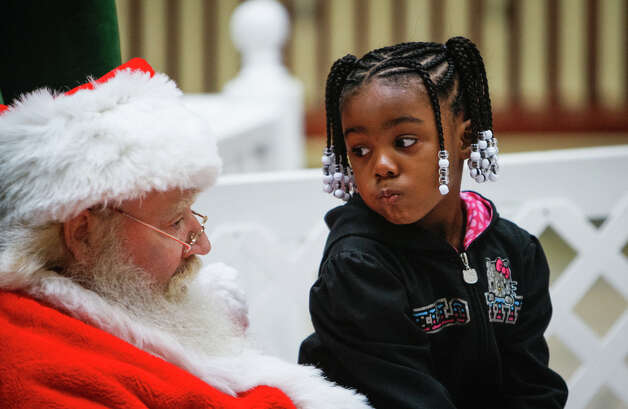 Iyona Sansbury, 4, of Columbia, South Carolina, thinks about what she wants for Christmas while sitting on Santa's lap at Dutch Square Center, Columbia, South Carolina, Thursday, December 20, 2012. Photo: Tim Dominick, McClatchy-Tribune News Service / The State
