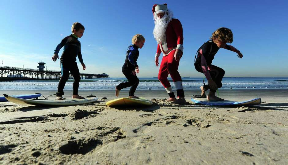 Surfing Santa, Michael Pless, 62, instructs his young students Luke Thompson (L), Damen Daugherty (C