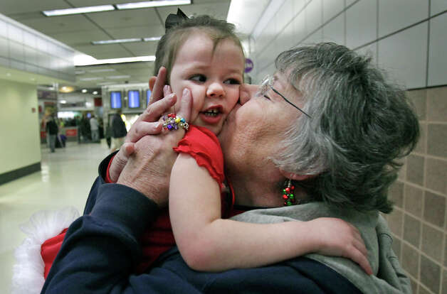 Cali Cash, age 2, is smothered with kisses from her grandmother Jorgene Hahner, after Hahner and her husband James Hahner arrived at the San Antonio International Airport from Atlanta.  Dec. 21, 2012 Photo: Bob Owen, San Antonio Express-News / ©SAN ANTONIO EXPRESS-NEWS