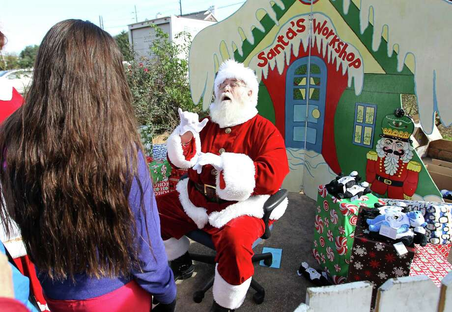 Santa a.k.a. Jim Pogue signs with deaf student, Brenda Cruz, 12, as she tells him what she wants for Christmas during  the Be An Angel Fund's 21st Annual Snow Day at T.H Rogers School. Photo: Karen Warren, Houston Chronicle / © 2012 Houston Chronicle