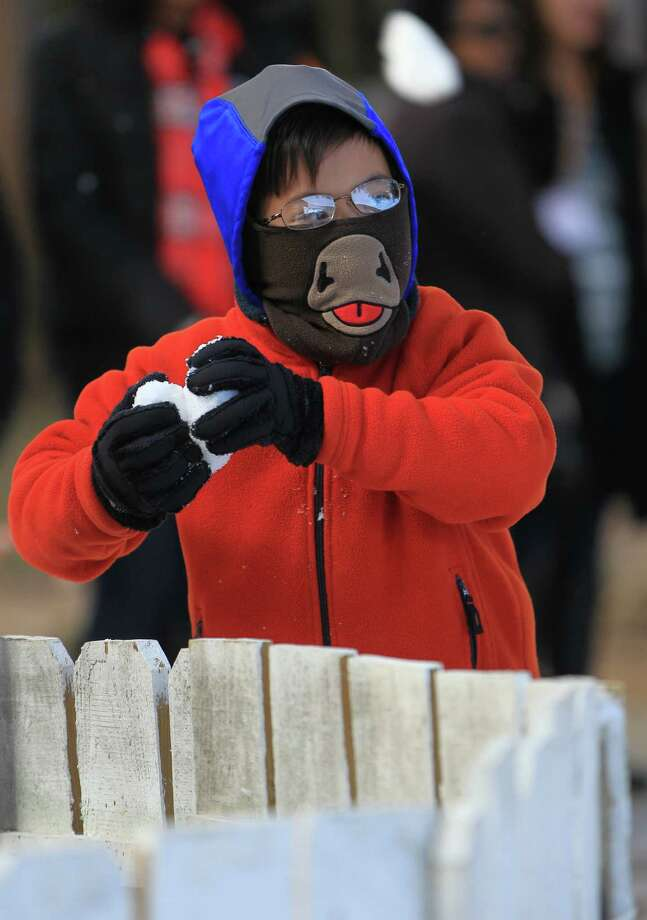 Fourth-grader Kevin Vo prepares to throw a snowball during Be An Angel Fund's 21st Annual Snow Day at T.H Rogers School. Photo: Karen Warren, Houston Chronicle / © 2012 Houston Chronicle