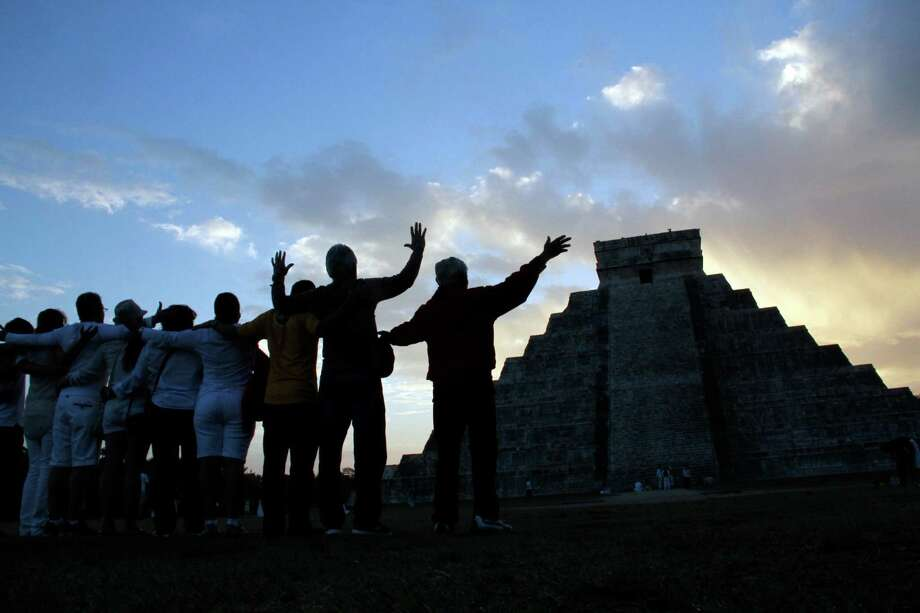People gesture toward the the Kukulkan temple in Chichen Itza, Mexico, Friday, Dec. 21, 2012. Ceremonial fires burned and conches sounded off as dawn broke over the steps of the main pyramid at the Mayan ruins of Chichen Itza Friday, making what many believe is the conclusion of a vast, 5,125-year cycle in the Mayan calendar. Some have interpreted the prophetic moment as the end of the world. The hundreds gathered in the ancient Mayan city, however, said they believed it marked the birth of a new and better age. (AP Photo/Israel Leal) Photo: Israel Leal, Associated Press / AP