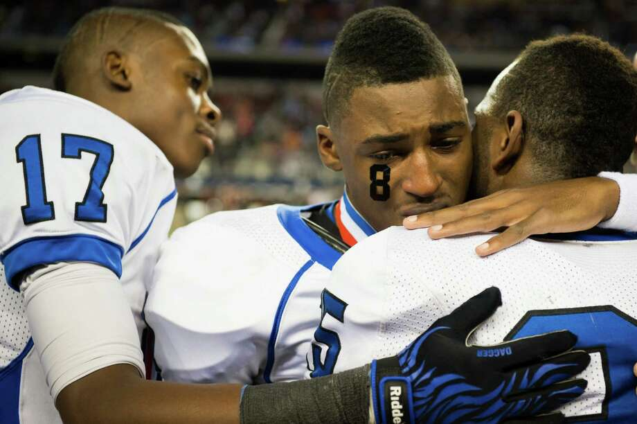 Navasota's Willie Creeks wears the number of his brother Xavier Creeks (8) on his cheek as he is hugged by teammates Howard Horn (25) and Terrance Creeks (17) after a 39-3 victory over Gilmer. Photo: Smiley N. Pool, Houston Chronicle / © 2012  Houston Chronicle
