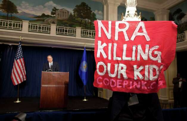 A protester holds up a sign as National Rifle Association executive vice president Wayne LaPierre, left, speaks during a news conference in response to the Connecticut school shooting on Friday, Dec. 21, 2012 in Washington. (AP Photo/ Evan Vucci) Photo: AP, STF / AP2012