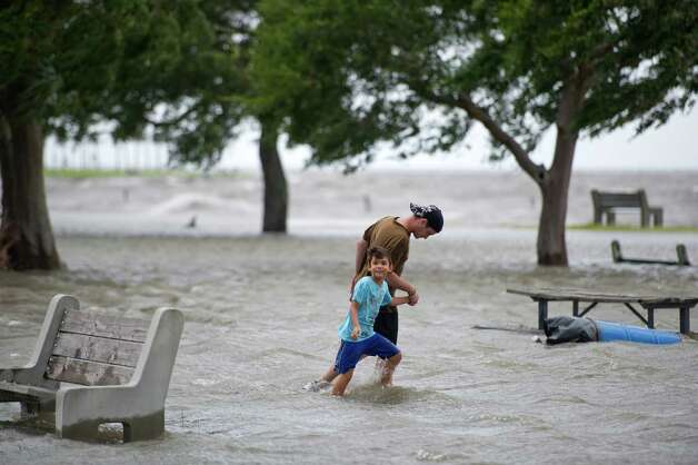 NEW ORLEANS, LA - AUGUST 28: Chris Rabin walks with Tyler Guevara through the flooded walkway along Lakeshore Drive as the waves grow higher on Lake Pontchartrain as Hurricane Issac rolls in on August 28, 2012 in New Orleans, Louisiana. (AP Photo/The Christian Science Monitor, Ann Hermes) Photo: Ann Hermes, Express-News / AP2012