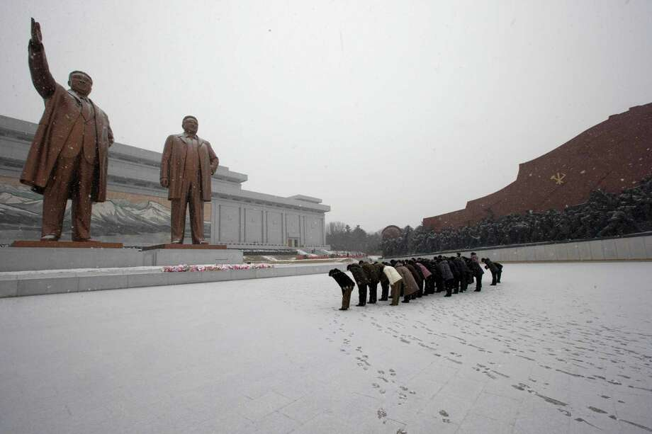 North Koreans bow in front of the statues of late North Korean leaders Kim Il Sung, left, and Kim Jong Il at Mansu Hill as it snows in Pyongyang, North Korea, Friday, Dec. 21, 2012. (AP Photo/Ng Han Guan) Photo: Ng Han Guan