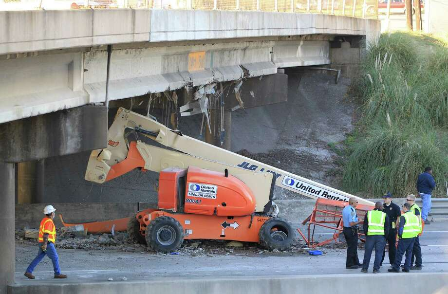 Investigators work to clear a two-vehicle accident on I-10 East, which caused a piece of heavy equipment to strike the Waco Street bridge overpass, causing damage to it and closing three main lanes, Friday, Dec. 21, 2012, in Houston. The freeway will be shut down this weekend to make repairs to this bridge. Photo: Karen Warren, Houston Chronicle / © 2012 Houston Chronicle