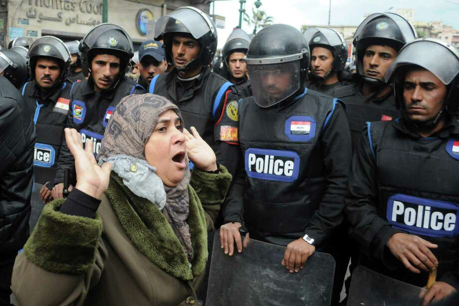 A woman reacts as she stands before riot policemen separating opponents of Egyptian President Mohammed Morsi clashing with Islamist supporters of the president in Alexandria, Egypt, Friday, Dec. 21, 2012. Thousands of Islamists clashed with their opponents Friday in Egypt's second largest city, Alexandria, on the eve of the second leg of voting on the country's contentious constitution that has deeply polarized the nation.(AP Photo) Photo: Anonymous