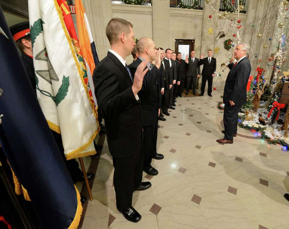 A new class of Albany firefighters was sworn in by Albany Mayor Jerry Jennings, right in the rotunda of Albany City Hall in Albany, N.Y. Dec. 21, 2012.    (Skip Dickstein/Times Union) Photo: Skip Dickstein / 00020551A