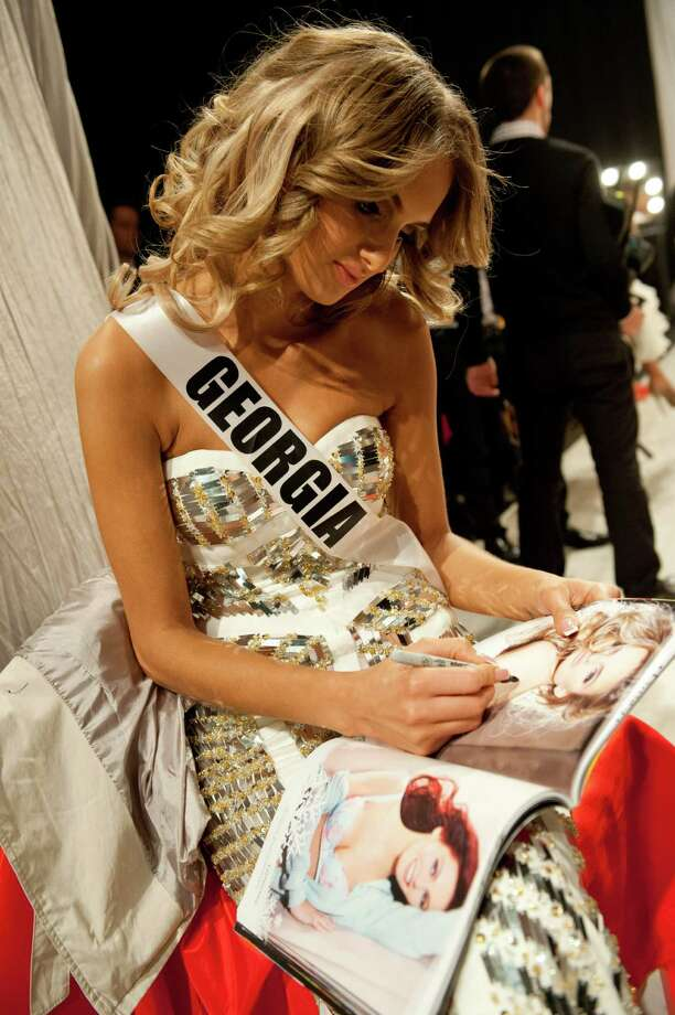 Miss Georgia, Tamar Shedania, signs a program backstage. Photo: Valerie Macom, Miss Universe Organization / Miss Universe Organization