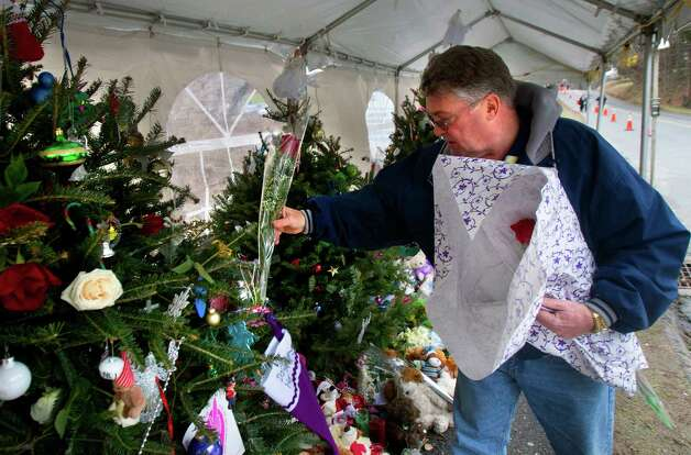 "Long Island Navy Veteran Michael Kennedy places a rose on a Christmas tree at a memorial in front of Sandy Hook Elementary School, Friday, December 21, 2012 in Newtown, Connecticut. Kennedy placed a rose on each of the 26 trees for each person who died after gunman Adam Lanza opened fire killing 26 individuals, 20 whom were children, last Friday. ""I have to do this before I'm dedicated to ridding our society of guns,"" Kennedy said. ""I'm going to do whatever I can to ban assault weapons and multiple clips. Our society is not defined by the NRA. It should never be defined by any extremist group. I consider them extremist."" Photo: Cody Duty, Cody Duty/Hearst Newspapers / The News-Times"