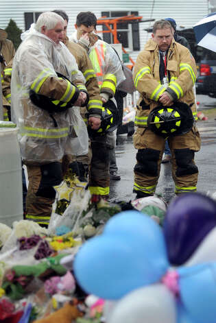 Members of the Sandy Hook Fire and Rescue Company gather for a moment of remembrance in front of a memorial to victims Friday morning as bells toll at 9:30a.m. all around the state, Dec. 21, 2012. Photo: Carol Kaliff / The News-Times