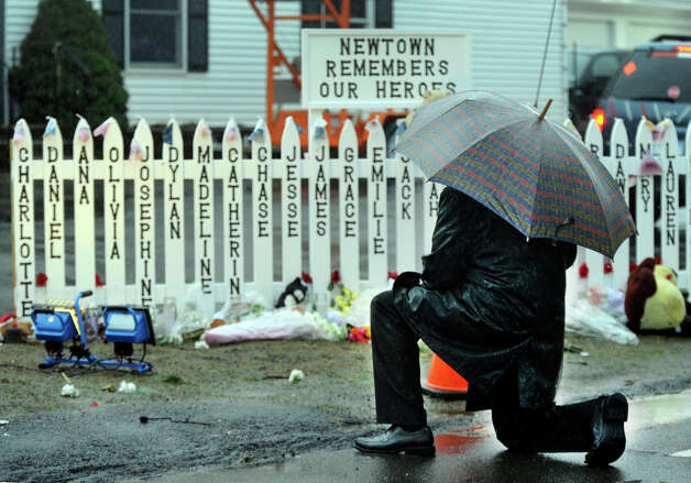 On Friday, Dec. 21, 2012, a week after the massacre, a man visits a memorial to those who died in the Sandy Hook Elementary School shooting in Newtown, Conn. last Friday. Photo: Carol Kaliff / The News-Times