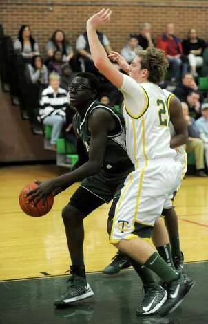 Norwalk's Roy Kane takes a shot as he is defended by Trinity Catholic's Dan O'Leary during Friday's boys basketball game at Trinity Catholic High School in Stamford on December 21, 2012. Photo: Lindsay Niegelberg, Niegelberg / Stamford Advocate