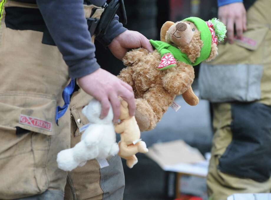 Firefighters rearranged flowers and teddy bears which were left by mourners outside Sandy Hook Elementary School, Sunday Dec. 16, 2012. (Will Waldron/Times Union) Photo: Will Waldron