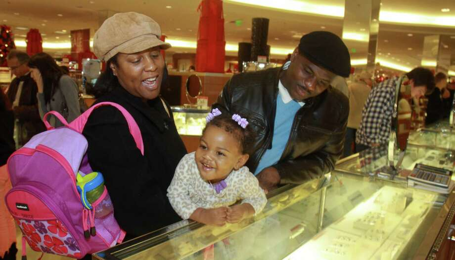 (For the Chronicle/Gary Fountain, December 21, 2012)   Samille and Terry Savoie, with their daughter, Havlyn, 13-months-old, shopping at the fine jewelry department at Macy's Memorial City Mall. Photo: Gary Fountain, Freelance / Copyright 2012 Gary Fountain.