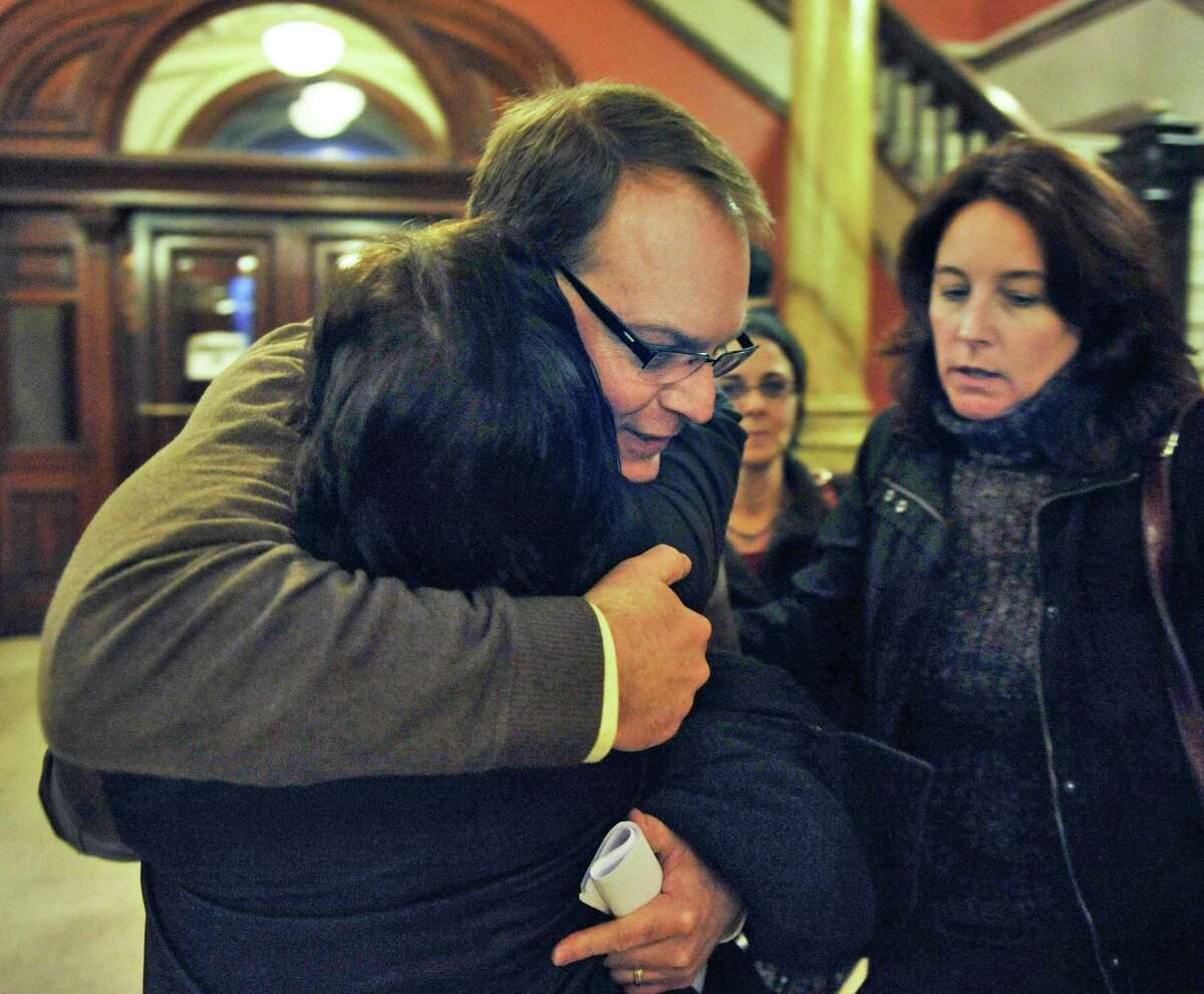 Ed McDonough gets a hug from a supporter outside Rensselaer County Court after being found not guilty in his ballot fraud case Friday Dec. 21, 2012. At right is McDonough's wife Jackie. (John Carl D'Annibale / Times Union)