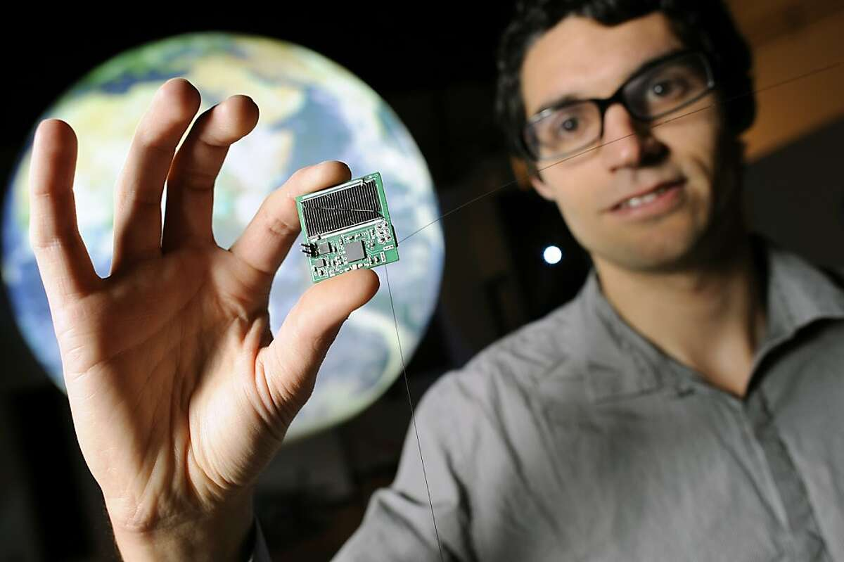 """Zac Manchester stands in front of a globe holding one of his """"micro satellites"""" that he has developed."""