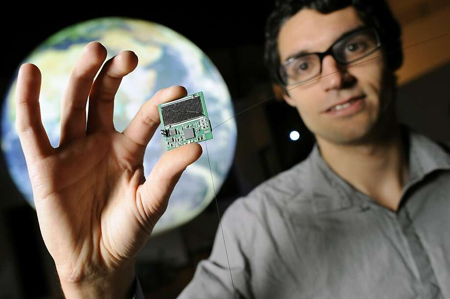 "Zac Manchester stands in front of a globe holding one of his ""micro satellites"" that he has developed. Photo: Michael Short, Special To The Chronicle"