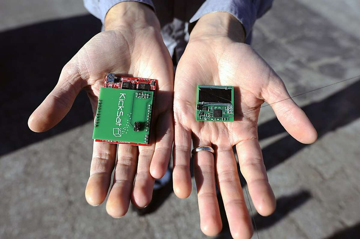 """Zac Manchester holds one of his """"micro satellites""""(R) and it's programming module that he has developed utilizing funding from Kickstarter, at the NASA Ames Museum in Mountain View, CA Thursday December 20th, 2012."""