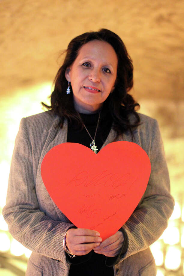 Patricia Doria holds a paper heart that people have been signing that's to be sent to Newtown, Conn. Photo: JENNIFER WHITNEY, Express-News / © Jennifer Whitney