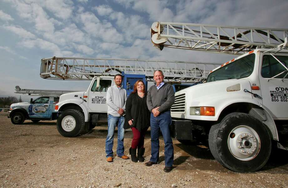 "12/10/12: From left to right, Patrick O'Day, Amy Matejek and Mike O'Day with Drilling Rig trucks and a Service Rig Truck at 5923 County Road 931, Rosahron, Texas. The company--which drills water wells--is celebrating its 100th year in business and just received an award from Baylor called the ""Texas Family Business of the Year: Founder's Award."" Photo: Thomas B. Shea / © 2012 Thomas B. Shea"