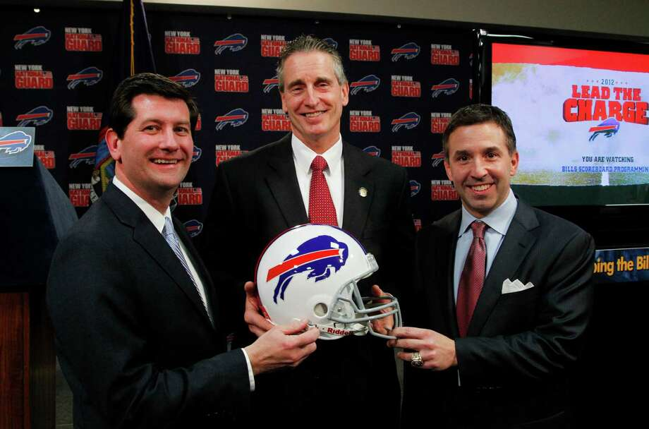 Erie County County Executive Mark Poloncarz, left, New York Lt. Gov. Robert Duffy, enter, and Buffalo Bills CEO Russ Brandon hold a Bills helmet at a news conference announcing details of a 10-year lease to keep the NFL football team in Orchard Park, Friday, Dec. 21, 2012, in Orchard Park, N.Y. (AP Photo/Bill Wippert) Photo: Bill Wippert