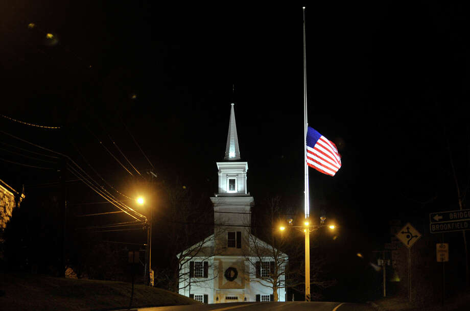 The flag pole on Main Street in Newtown flies at half-mast on Friday, Dec. 21, 2012, one week after the Sandy Hook Elementary School shooting. Photo: Jason Rearick / The News-Times