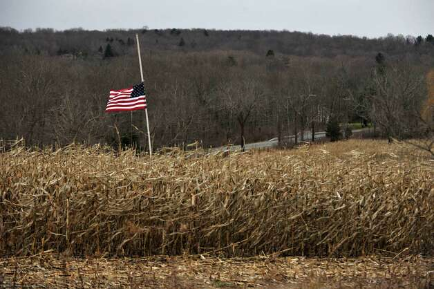 A flag pole in the middle of a corn field near Sugar Street in Newtown flies at half-mast on Friday, Dec. 21, 2012, one week after the Sandy Hook Elementary School shooting. Photo: Jason Rearick / The News-Times