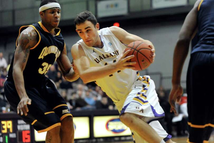 UAlbany's Sam Rowley (14), center, drives past Quinnipiac's Jamee Jackson (35) during their basketba