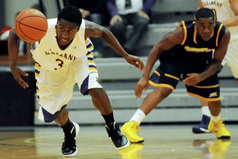 UAlbany's D.J. Evans (3), left, chases a loose ball during their basketball game against Quinnipiac