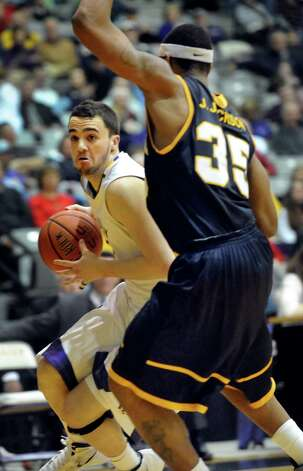 UAlbany's Peter Hooley (12), left, drives for the hoop as Quinnipiac's Jamee Jackson (35) defends during their basketball game on Friday, Dec. 21, 2012, at UAlbany in Albany, N.Y. (Cindy Schultz / Times Union) Photo: Cindy Schultz / 00020487A