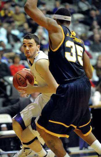 UAlbany's Peter Hooley (12), left, drives for the hoop as Quinnipiac's Jamee Jackson (35) defends du