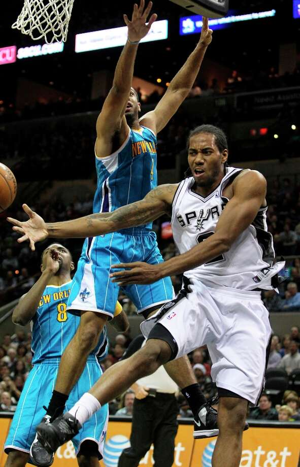 Spurs forward Kawhi Leonard passes off for an assist under the basket as San Antonio plays the New Orleans Hornets at the AT&T Center on December 21, 2012. Photo: Tom Reel, San Antonio Express-News / ©2012 San Antono Express-News