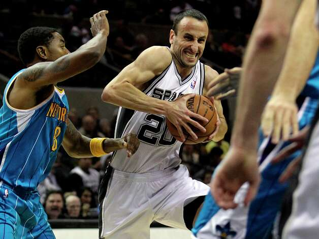 Spurs guard Manu Ginobili drives into the lane past Roger Mason, Jr. as San Antonio plays the New Orleans Hornets at the AT&T Center on December 21, 2012. Photo: Tom Reel, San Antonio Express-News / ©2012 San Antono Express-News