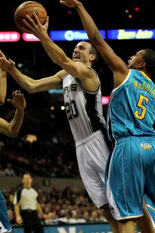 Manu Ginobili gets a layup by Dominic McGuire as San Antonio plays the New Orleans Hornets at the AT&T Center on December 21, 2012. Photo: Tom Reel, San Antonio Express-News / ©2012 San Antono Express-News
