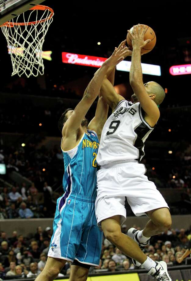Tony Parker twists in for a shot over the Hornet's Daruius Miller, drawing a foul in the first half as San Antonio plays the New Orleans Hornets at the AT&T Center on December 21, 2012. Photo: Tom Reel, San Antonio Express-News / ©2012 San Antono Express-News