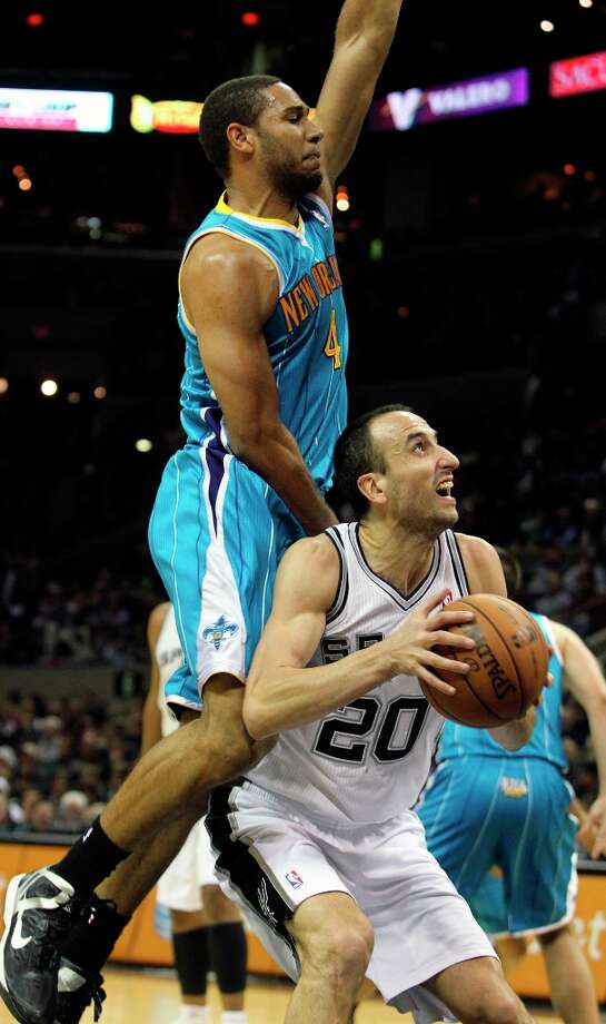 Spurs guard Manu Ginobili draws a foul on Xavier  Henry after faking him off his feet as San Antonio plays the New Orleans Hornets at the AT&T Center on December 21, 2012. Photo: Tom Reel, San Antonio Express-News / ©2012 San Antono Express-News