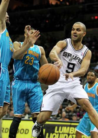Tony Parker dishes away after getting under the basket as San Antonio plays the New Orleans Hornets at the AT&T Center on December 21, 2012. Photo: Tom Reel, San Antonio Express-News / ©2012 San Antono Express-News
