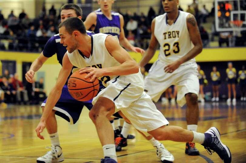 Troy's Imre Megyeri (22), center, drives past CBA's Drew Brundige (31) during their basketball game