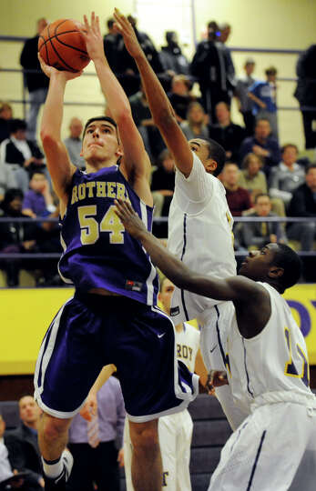 CBA's Greig Stire (54), left, shoots for the hoop during their basketball game against Troy on Frida