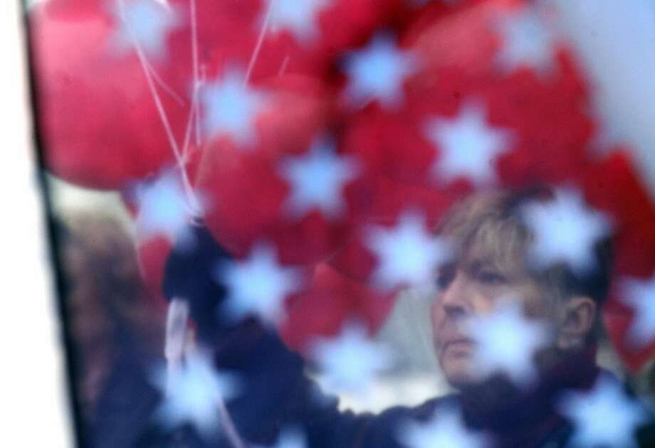 People gather at the Colonial Beach American Legion Post to mark the eighth anniversary of the suicide bombing in Mosul, Iraq that took the lives of Sgt. David Ruhren of Stafford and Sgt. Nick Mason of King George, by releasing red balloons into the air precisely at 12:00 noon on Friday, Dec. 21, 2012. Earlier in the day, they also released balloons to mark the one-week old attack that occurred in Newtown, Conn. Photo: Reza A. Marvashti, Associated Press