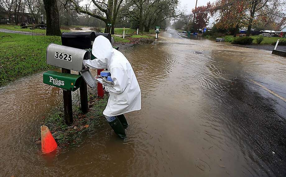 Sandy LeDuc braves floodwaters to gather her mail on Piner Road, Friday Dec. 21, 2012 in Santa Rosa, Calif as a large winter storm barreled in to Northern California. Photo: Kent Porter, Associated Press