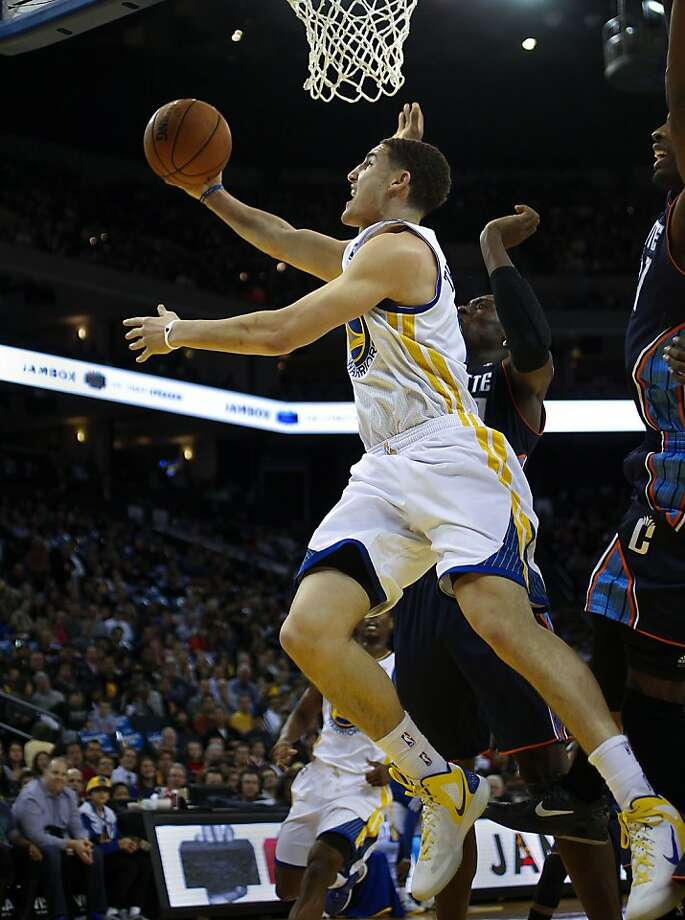Warriors Klay Thompson, (11) sneaks inside the Bobcats Bismack Biyombo, (0) in the first quarter, as the Golden State Warriors take on the Charlotte Bobcats in NBA action in Oakland, Calif. on Friday Dec. 21,2012. Photo: Michael Macor, The Chronicle