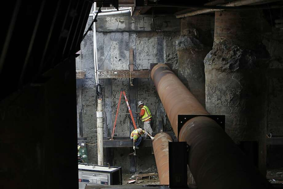 Workers climb  along the struts to make sure the construction is properly secure under the ground where the excavation is being done  down to build the new Transbay Terminal site, Monday Dec. 17, 2012, in San Francisco, Calif. Photo: Lacy Atkins, The Chronicle