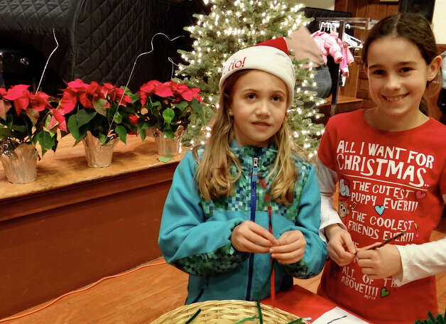 Fairfielders Maddie David and Kayla Thomson, both 9, make pipe cleaner candy canes Fridayt at Pequot Library's holiday party.  Fairfield CT 12/21/12 Photo: Mike Lauterborn / Fairfield Citizen contributed