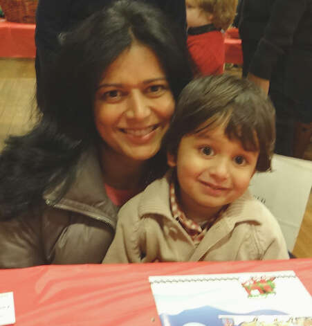 Parul Pomichter, of Fairfield, and her son, Krish, 3, collaborate on a craft at Pequot Library's holiday party on Friday.  Fairfield CT 12/21/12 Photo: Mike Lauterborn / Fairfield Citizen contributed